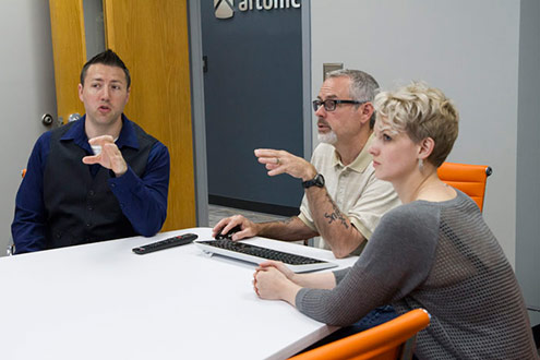 Three people discuss ideas in a conference room; image shows an example of how to take a great picture with a mobile phone.