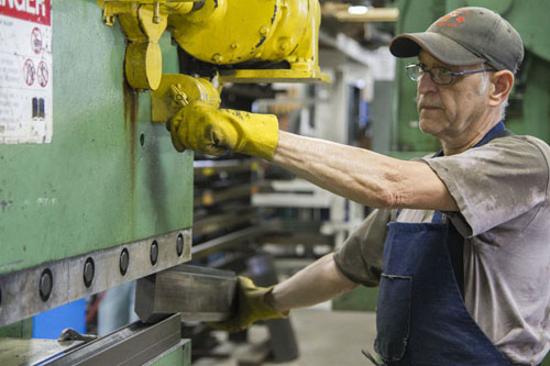 A man at AGET Manufacturing in Michigan runs a machine