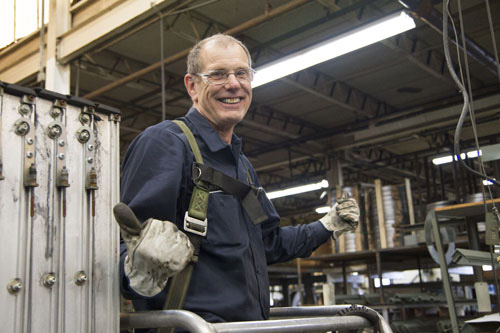 Michigan manufacturing worker smiles and gives thumbs up