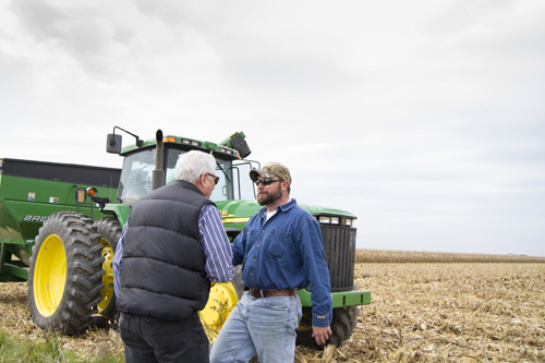 Men shake hands in a corn field for website photo shoot in southeast Michigan