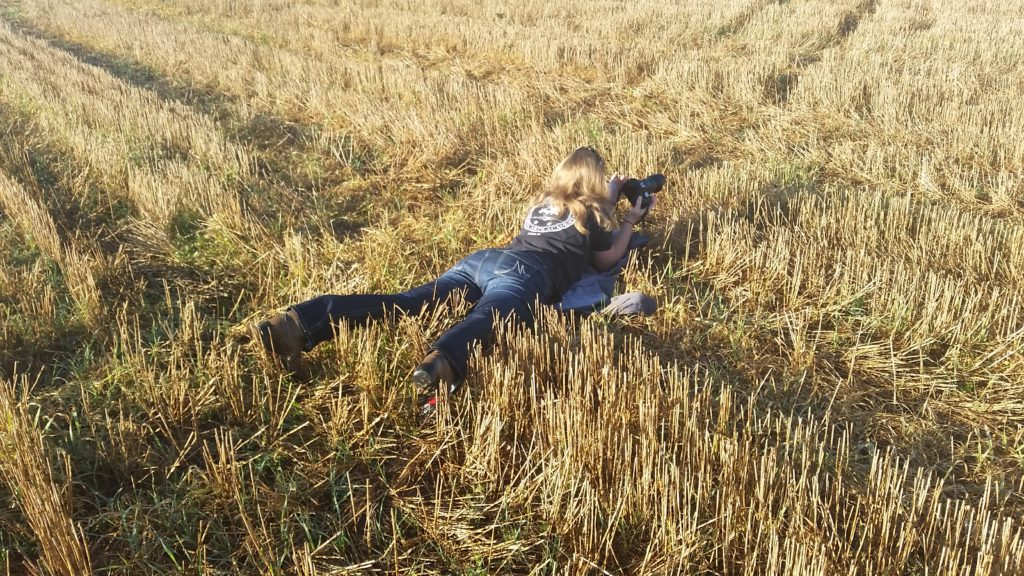 Woman lays in field with camera.