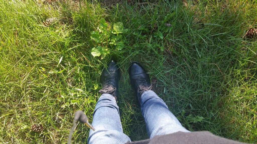 Woman's booted feet in grass.