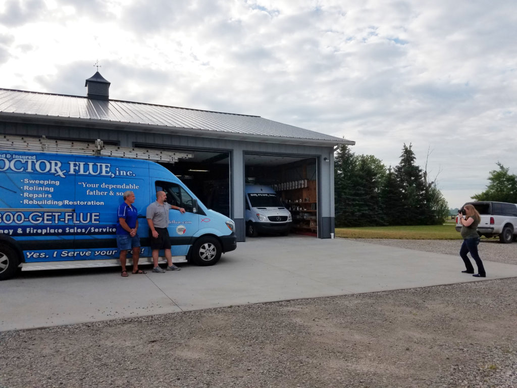 Woman photographs business owner in front of a work van.