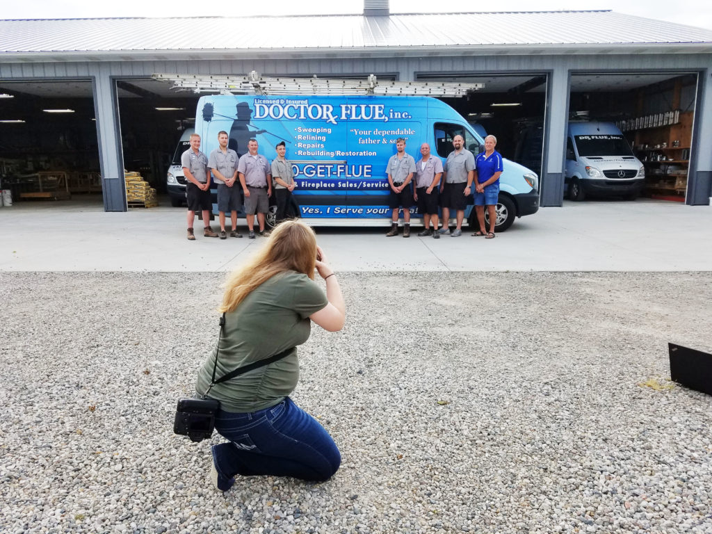 The techs line up in front of a brightly branded van.