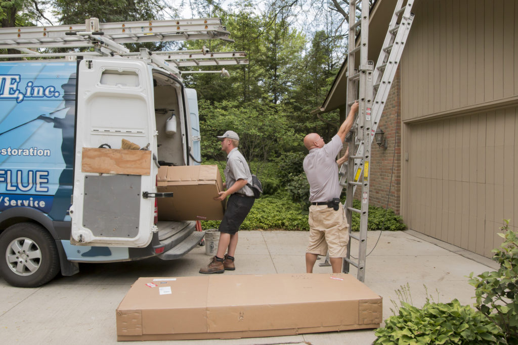 Techs work to load a ladder into a work van.