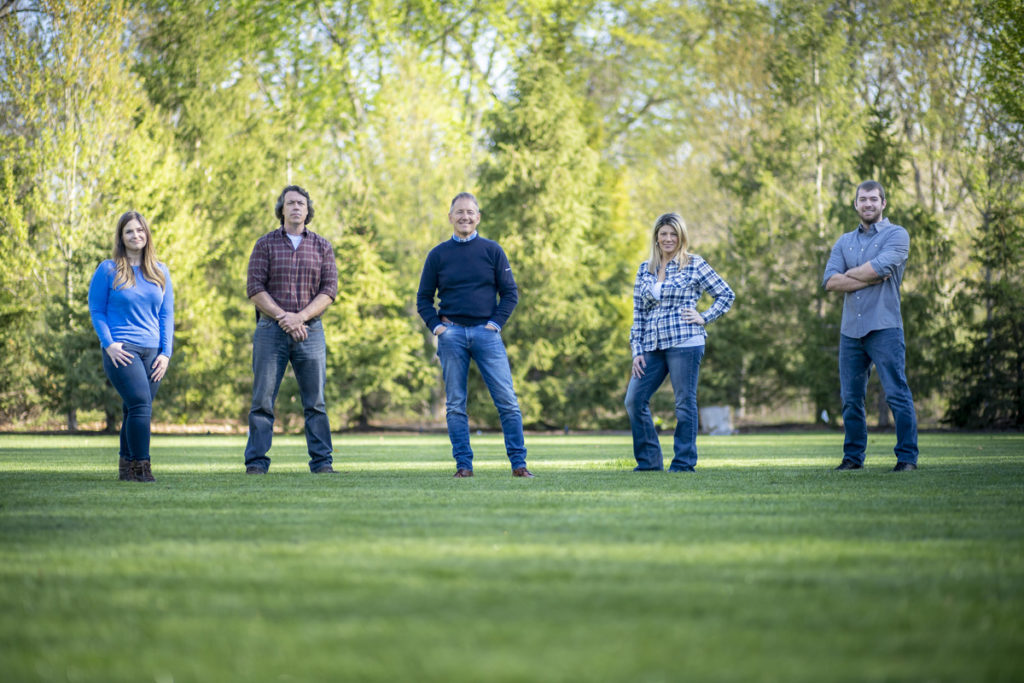 Portrait of five people standing on green grass in the sunlight.