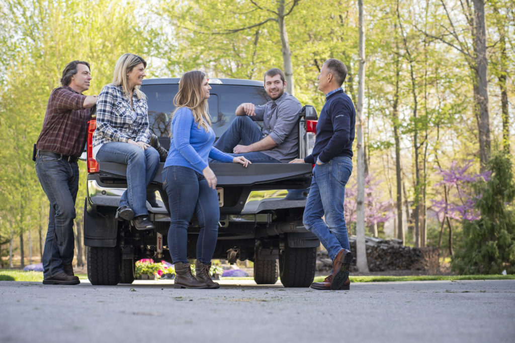 People stand and talk, gathered around a work truck.
