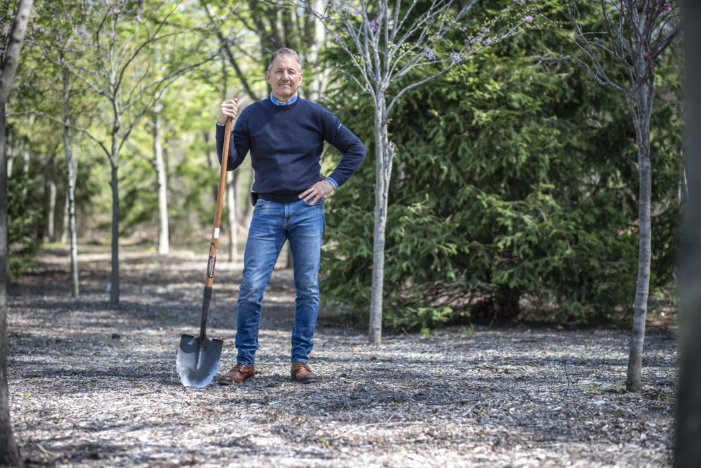Ken stands with hand on hip, shovel in hand.